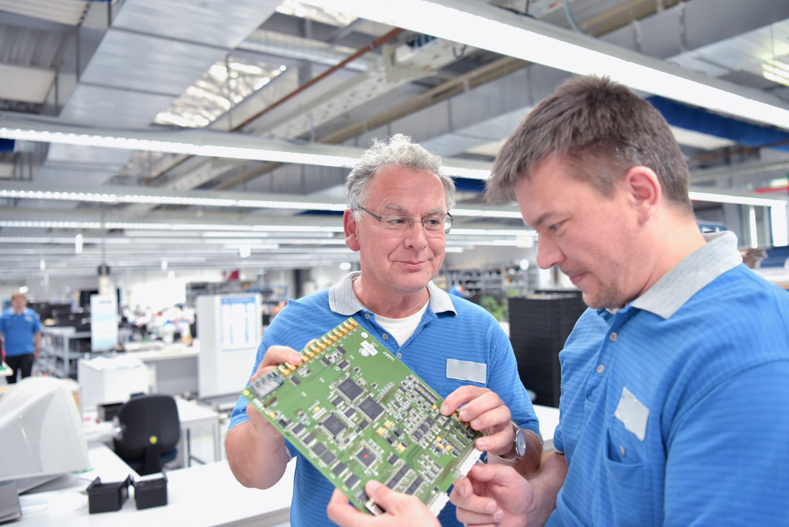Teamwork: Techniker in der Elektronikfabrik bei Besprechnung über Fertigung von Platinen //  Technician in the electronics factory discussing the manufacture of printed circuit boards